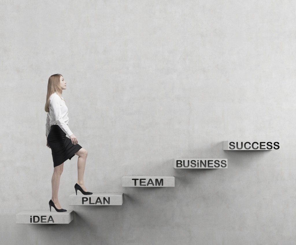 Young business woman is going up to the stairs. A concept of successful business project